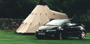 A car parked in front of a large tent