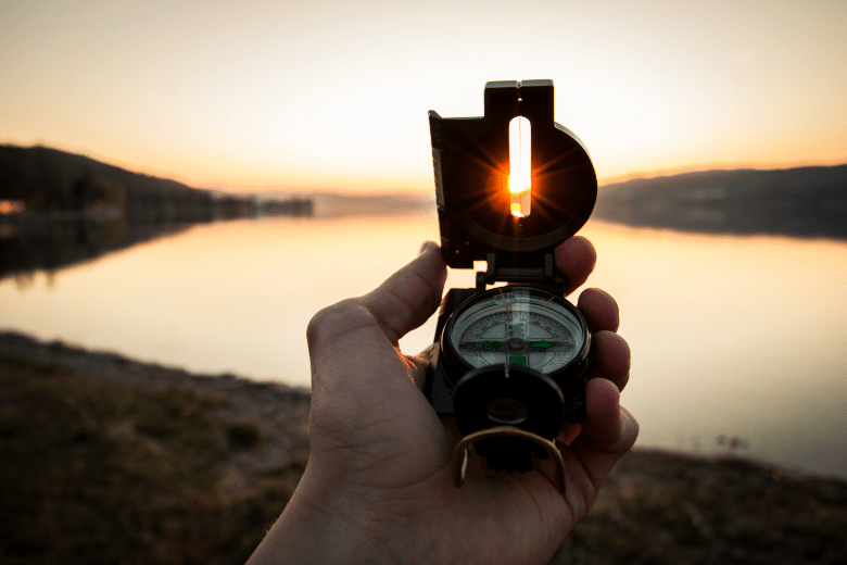 A person holding up a compass towards the sun during sunset