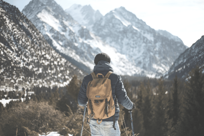 man looking at a mountain valley while wearing layered clothing