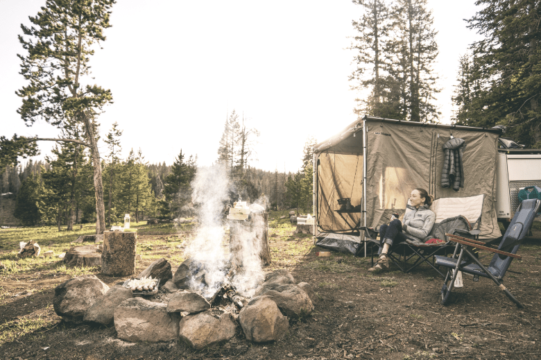woman sitting near a campfire and her tent